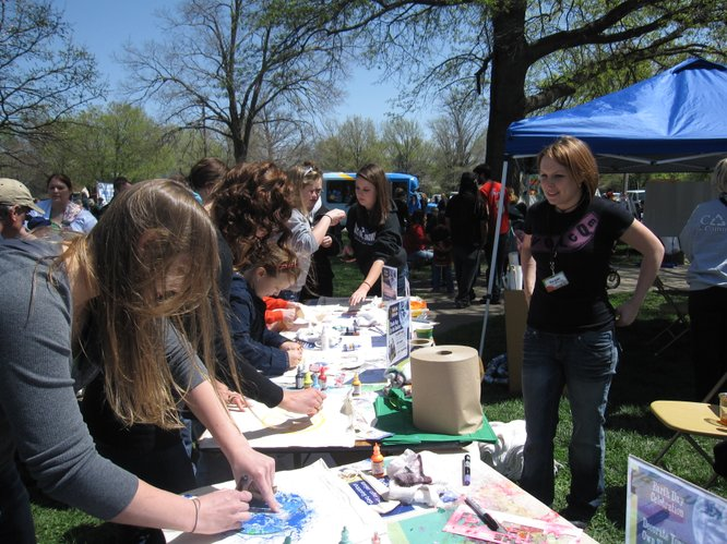 Regan Ramp, left, watches over The Merc's booth at the Earth Day Celebration in South Park. People were decorating reusable shopping bags. By Earth Day, April 22, The Merc — at Ninth and Iowa streets — will no longer carry plastic bags.