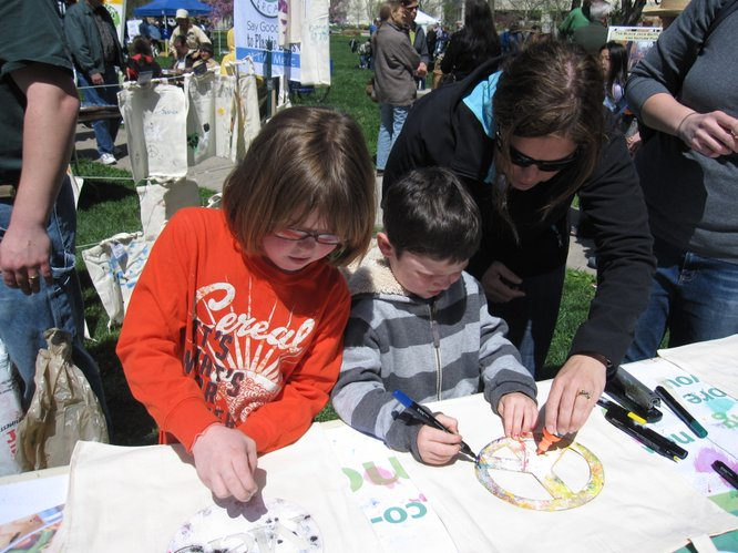 From left, Ella Diederich, 8, and her brother Owen, 5, decorate reusable bags with some help from their mom, Becca Diederich. They were at The Merc's booth at the Earth Day Celebration on Saturday, April 16, 2011, at South Park.