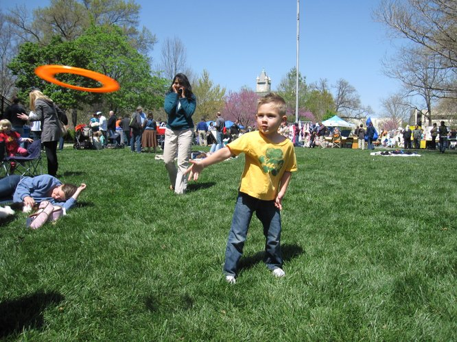Blaise Brewer, 5, of Lawrence, tosses a Frisbee to his mom, Alice, at the Earth Day Celebration in South Park.