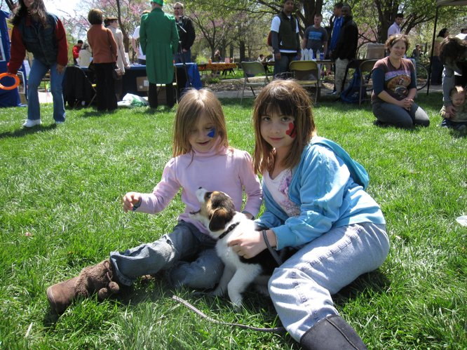 Lexi Grigg, 7, left, and Emily Esparza, 9, play with Lexi's new 9-week-old puppy in South Park during the Earth Day Celebration. The puppy's name will be Suzy or Susie — the family hasn't decided yet.