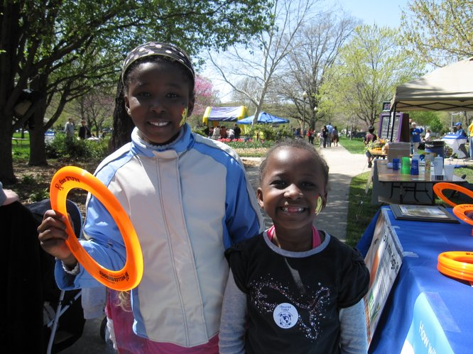 Thayu Kimori, 8, and her sister Wendo, 6, both of Lawrence, picked up Frisbees at the WellCommons booth during the Earth Day Celebration in South Park.