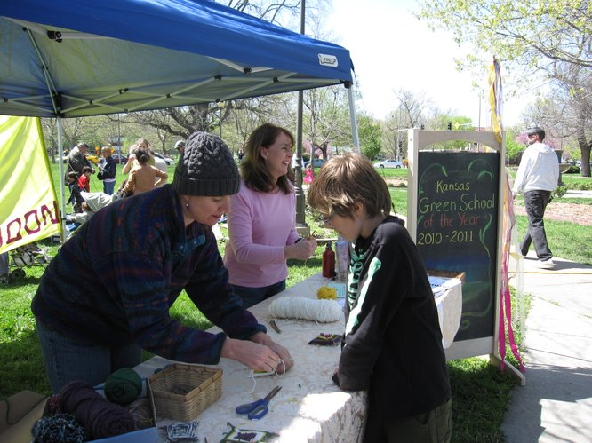 Prairie Moon Waldorf School, which recently was named a Kansas Green School of the Year, had a booth at the Earth Day Celebration in South Park. From left, Dana Atwood-Blaine and Amy Stevenson, teach Raiden Garcia, 11, Lawrence, how to make a God's Eye. It is made from yarn and two sticks.