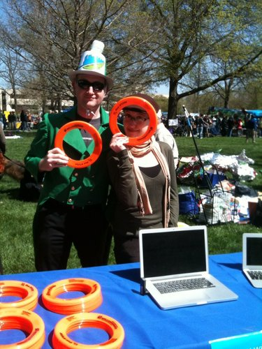 Jonathan Kealing and Jessica Schilling, of The World Company, hand out Frisbees during Earth Day activities Saturday, April 16, 2011, in South Park. They were at the booth for WellCommons and SunflowerHorizons, two community-based websites. WellCommons recently celebrated its one-year anniversary and it about wellness.