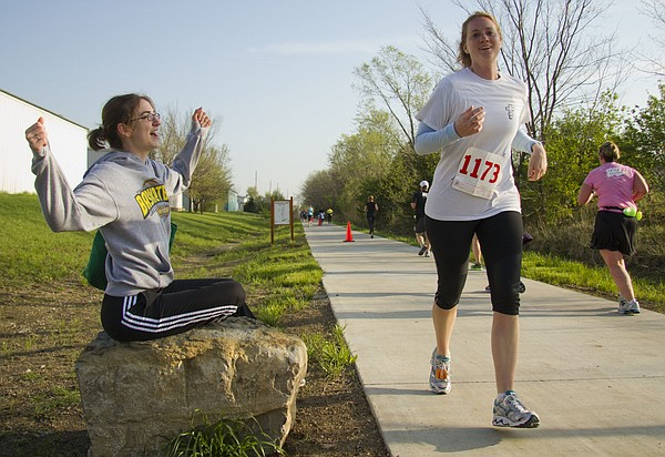 Mary Beth Rader, Topeka, seated, cheers on her sister, Jennifer Urton, Waverly, as Urton competes in the 10K race of the Kansas Half Marathon along the Burroughs Creek Trail on Sunday, April 17, 2011.