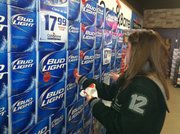 """Free State High junior Ruthie Ozonoff places warning stickers on cases of beer Saturday at Cork & Barrel, 2000 W. 23rd St. Ozonoff and about three dozen other area students spent the morning adding the stickers as part of """"Sticker Shock Lawrence,"""" an event designed to discouraged underage drinking."""