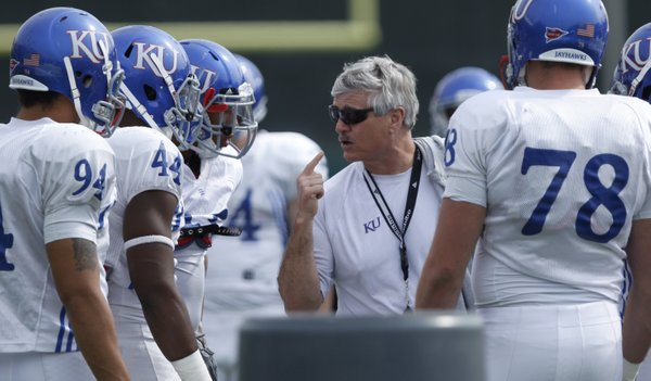 Kansas defensive coordinator Carl Torbush gets in the huddle for some instruction during football practice on Monday, April 18, 2011 at the practice fields near Memorial Stadium.