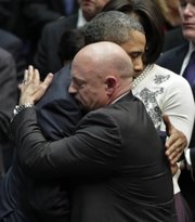 President Barack Obama embraces Mark Kelly, right, the husband of critically wounded Rep. Gabrielle Giffords, D-Ariz., at the end of a ceremony honoring the victims of a shooting rampage in this Jan. 12 file photo. Kelly said his wife has received permission from doctors to attend the launch of the Endeavour on Friday, the last trip for the shuttle and the next-to-last shuttle mission.