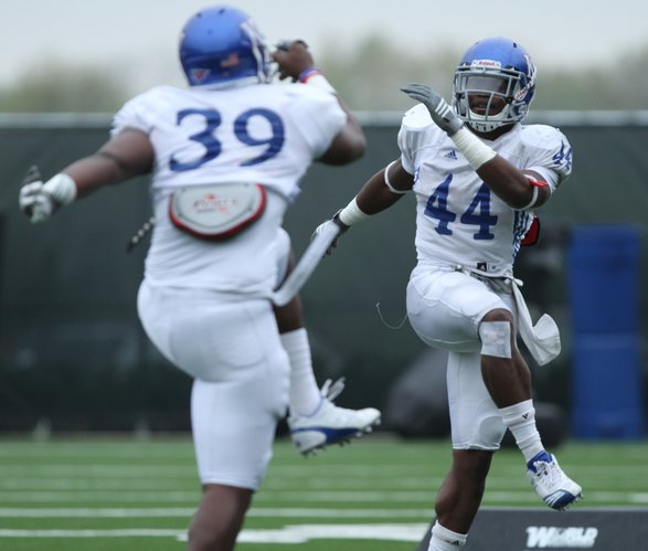 Kansas linebackers Malcolm Walker (44) and Darius Willis (39) stretch as they run through drills during practice on Monday, April 25, 2011 at the practice fields near Memorial Stadium.