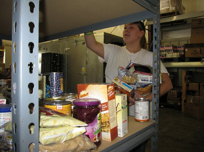 Volunteer Amanda Elkins, Lawrence, moves food donations from a storage shelf in the back of the Just Food warehouse to shelves in the front. Food pantry clients get to pick four speciality items during their monthly visit.