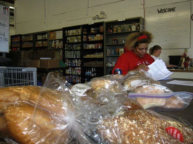 Nicole Dyke, forefront, and Amanda Elkins are both volunteering at the Just Food pantry on Thursday, April 28, 2011. Thanks to $80,000 in community donations the pantry — which serves about 1,500 people each month — will remain open.