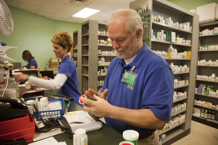 Pharmacist Ken Wood and Alicia Norton fill prescriptions  for patients at the Community Health Center of Southeast Kansas in Pittsburg. The on-site pharmacy helps create a one-stop shop for patients.