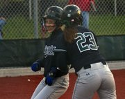 Free State's Katy Davis, left, and Elizabeth Hazlett celebrate at the plate after both scored against Shawnee Mission North on Thursday, May 5, 2011 at FSHS.