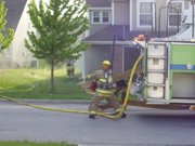 In this user-submitted photo taken by Lawrence resident Paul Goebel, firefighters rush to put out a fire in the 400 block of John Doy Court, Wednesday, May 4, 2011. The fire displaced a family of four and caused $76,000 in damage.