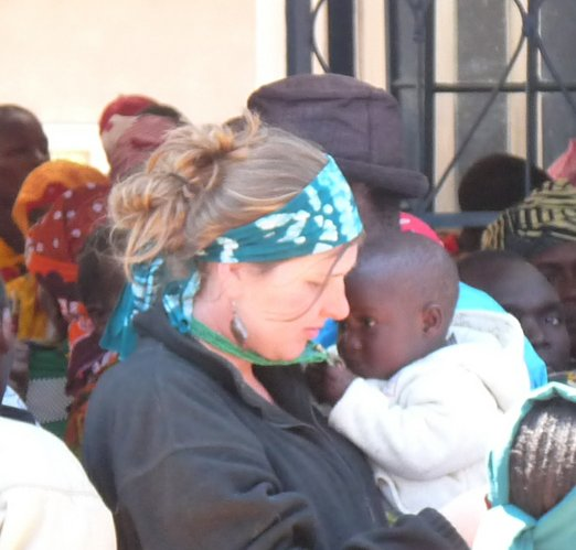 Jenny Peck, a Kansas University graduate, is holding Melania, one of the children at the children's village in Mufini, Tanzania. They were at a clinic where Melania was getting tested for HIV/AIDS. She was negative.