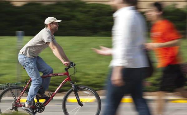 Doug Nickel, a coordinator of multimedia advertising at Kansas University, cruises down Jayhawk Boulevard on his way home from work Tuesday, May 10, 2011. Nickel has biked to work since 1996, and to KU since 2008, when he began working there.