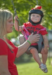 "Courtlynn ""Coco"" Shutt, 2, swings next to her mother, Ali Shutt, of Eudora, Thursday outside the Eudora Community Center where area officials were meeting with Kansas Department of Transportation officials to discuss Kansas Highway 10 safety issues between Kansas City and Lawrence. Courtlynn suffered a broken vertebra in a crossover crash on K-10 near Eudora on April 16 that killed her brother, Cainan Shutt, 5. Family and friends held a candlelight memorial for Cainan during the KDOT meeting. See a video of the memorial service at LJWorld.com."