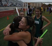 Free State senior Hayley Francis, right, hugs junior Lynn Robinson after Robinson pulled off a come-from-behind win during the finals of the s 4x800 relay at the Sunflower League Invitational on Friday, May 13, 2011 at Shawnee Mission North High School. Also pictured are relay teammates Molly McCord, back left, freshman, and Bailey Sullivan, freshman.