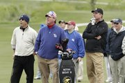 Roy Williams, left, and Bill Self, right front, watch as Notah Begay tees off on hole 14 at the celebrity skins game at Firekeeper Golf Course in Mayetta on Sunday, May 15, 2011.