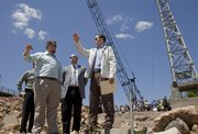 Gov. Sam Brownback, right, looks over the Kansas River and visits with Kellen Petersen, left and Jeff Thorn, center, both engineers with Olsson Associates, about the $20 million project to build a new hydroelectric power plant on the north bank of the Kansas River. A groundbreaking ceremony was held Monday for the project.