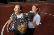 Lawrence High catcher Kristen Bell, left, and pitcher Lauren Massey can't contain their laughter during a photo shoot on Monday at the LHS softball field. The two seniors have lifted LHS from a one-win season in 2009 to 12-8 going into Tuesday's 4:45 p.m. game against Free State in Topeka.