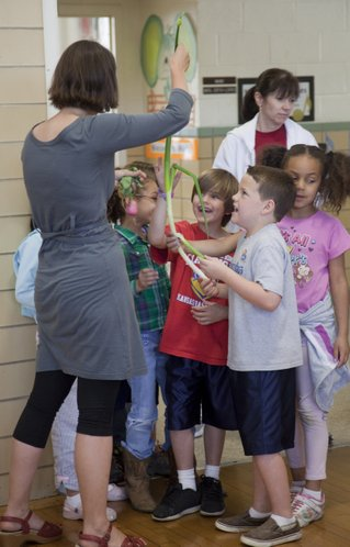 Cordley Elementary students admire the size of an onion plant held by school volunteer and parent Kelly Jones in the cafeteria Tuesday, May 17, 2011. For Tuesday's lunch, the students and staff ate fresh produce that the students had recently picked from Lawrence-area farms.