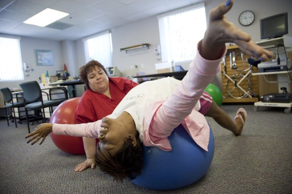 Tammie Riccardo, 39, Lawrence, lies on a balance ball in an exercise designed to help stretch muscles around scar tissue left from a double mastectomy, during a therapy session in May 2011 with occupational therapist Dana White at Kreider Rehabilitation Services South, 3510 Clinton Place. Riccardo, who is now cancer-free, was a participant in a clinical trial at Lawrence Memorial Hospital, which involved an intense chemotherapy treatment.
