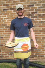 Lawrence resident Nick Frisby shows off the ginger scones he made for the Great American Bake Sale for Share Our Strength on May 14 and models a pillowcase apron made by Katie Kritikos.