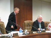 Gary Sherrer on Wednesday leaves the Kansas Board of Regents meeting after announcing his resignation from the panel. Seated is Vice Chair Ed McKechnie. Board members said they were shocked by Chairman Sherrer's decision.