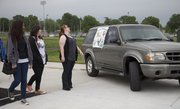 Lawrence high school students look over a Ford Explorer that will be given away in a drawing at Project Graduation. The vehicle was on display Friday, May 27, 2011, at the high school during a rehearsal for the LHS graduation ceremony Sunday.