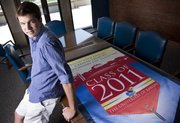 Kansas University graduating senior Mathew Shepard is pictured Monday with the class of 2011 banner, which he helped design.