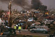 Emergency personnel walk through a neighborhood severely damaged by a tornado near the Joplin Regional Medical Center in Joplin, Mo., Sunday, May 22, 2011. A large tornado moved through much of the city, damaging a hospital and hundreds of homes and businesses.
