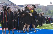Spectators watch as Kathryn Crumb, Blaire, Nebraska, back, and Kirin Arnold, Lawrence, go airborne for a chest bump in the endzone of Kivisto Field in the fashion of the KU football team, during the 2011 Commencement at Memorial Stadium on Sunday, May 22, 2011.