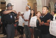 Capt. Leslie Robinson, left, with the Capitol police, asks protestors to leave the Capitol after Georgia Gov. Nathan Deal signed an immigration bill Friday, May 13, 2011, in Atlanta. Almost every state in the union decided to tackle immigration on its own this year in the absence of any federal action on the issue. But an Associated Press review of the data found that as of Wednesday almost all of the punitive measures failed.