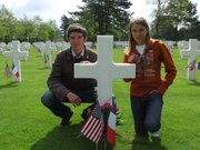 Alexandre and Eloise Maurouard pose beside the grave of Pvt. Elmo Banning on Memorial Day 2010.