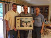 In 2009, Franck Maurouard, center, met with Elmo Banning, named for his uncle who was killed during D-Day, and Pvt. Banning's brother, Melvin. Maurouard is holding a tribute to Pvt. Banning, including his Purple Heart, photo and Ranger patch alongside a large photo of the Colleville sur Mer cemetery, where Pvt. Banning is buried.