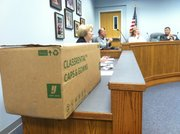 A box of rental gowns awaits distribution to members of the Lawrence school board, for use during 2011 commencement ceremonies. From left to right are Janice Dunn, board clerk; Rick Doll, superintendent of the Lawrence school district; Rich Minder, board president; and Mark Bradford, board vice president. Members received their gowns before their May 23 meeting at district headquarters, 110 McDonald Drive.