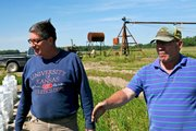 Farmers Mike Garrett, left, and Richard Brauer and Mike Garrett check the status of their tomato plants at the farm they work in Linwood, Kan. Brauer and Garrett have teamed up to cut production costs.