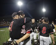 Lawrence High starting pitcher Alex Laughlin gets a hug from head coach Brad Stoll following the Lions' 2-1 win over Shawnee Mission West during the first round of the 6A state championships at Hoglund Ballpark.