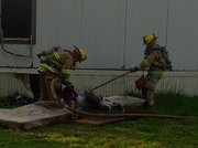 Firefighters work to extinguish a mattress after responding to a structure fire at Riverside Manufactured Home Community, 420 North St. in Lawrence on Sunday, May 29, 2011.