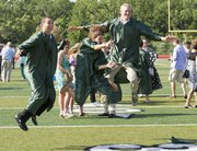 From left, Evan Manning, Hayley Francis and Austin Hoag celebrate their graduation from Free State High School by jumping for a photograph after the ceremony Sunday, May 29, 2011 at the Free State stadium.