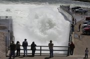 People watch water being released through the Oahe Dam's Stilling Basin near Fort Pierre, S.D., Saturday May 28, 2011. U.S. Army Corps of Engineers officials say they have to release more water than previously expected through the Missouri River dams because of expected heavy rains upstream. The corps now plans to maintain releases from Oahe Dam at the current level of 85,000 cubic feet a second until Thursday, June 2, 2011, and then step it up to 150,000 by mid-June - much higher than previously expected.