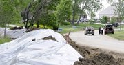 Residents load up possessions near a newly-created dirt levee Monday, May 30, 2011, in Dakota Dunes, S.D. Rising water from the Missouri River is threatening the planned community, which is under a voluntary evacuation order.