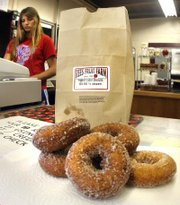 Karli Meier sells doughnuts at the Rees Farm store in Topeka May 31, 2011.  Topeka residents wanting one of the popular cider doughnuts from Rees Fruit Farm won't be able to get them at the farmers' market held every Wednesday on the Statehouse grounds.