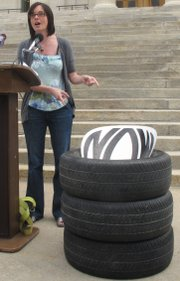 Kari Ann Rinker, Kansas state coordinator for the National Organization for Women, points out the tires she brought to a news conference to protest recent remarks by state Rep. Pete DeGraaf, a Mulvane Republican, Wednesday, June 1, 2011 outside the Statehouse, in Topeka. DeGraaf supports a new state law requiring women to buy separate health insurance policies if they want most abortions covered and compared buying them to having a spare tire on a car.