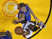 Miami's Chris Bosh, right, shoots over Dallas' Dirk Nowitzki in the second half. The Heat beat the Mavs, 92-84, in the first game of the NBA finals on Tuesday in Miami.