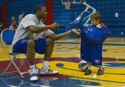 Kansas forward Thomas Robinson, left, helps 6-year-old Danny Phalen, of Lawrence, into some KU warmup gear during Bill Self's parent-child basketball camp Friday, June 3, at Allen Fieldhouse.