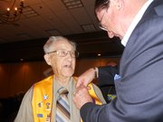 Ned Link receives an honorary pin from the International President of the Lions Club. Link, who is 96 years old, has been a member of the service club for 75 years.