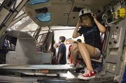 Bridget Cary, 15,  Lawrence, tries on a flight helmet as she sits inside a LifeStar helicopter during the 2011 Kansas Aviation Youth Camp at the Lawrence Municipal Airport.