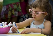 June Baggett, 4, was sporting her fancy glasses while coloring her boomerang during the One World, Many Stories summer reading program kickoff Saturday at the Lawrence Public Library.