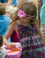 Allie Depperschmidt, 6, uses the sideways approach while coloring her boomerang during the One World, Many Stories summer reading program kickoff Saturday at the Lawrence Public Library.